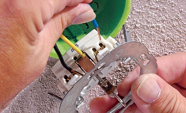 Elektriker tauscht Lichtschalter und steckt die Adern in Klemmlöcher