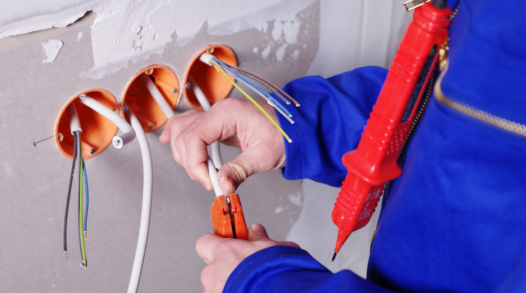 Elektriker isoliert Kabel aus Steckdose ab und repariert